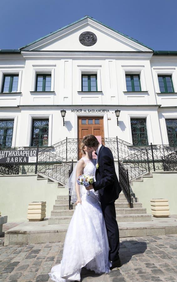 Les jeunes ont marié des couples, embrassant à côté du site architectural image libre de droits