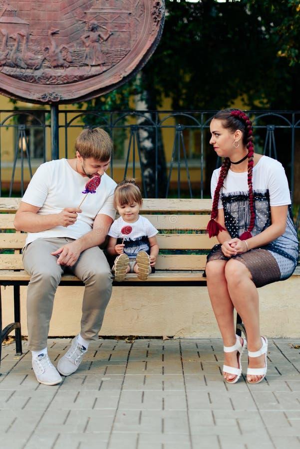 Les jeunes ont marié des couples sur le banc en parc, mère avec la fille avec la lucette dans des mains dans des robes d'une anné images stock