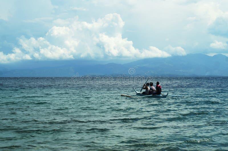 Les jeunes ont plaisir à monter sur le petit bateau minuscule sur la mer photo libre de droits