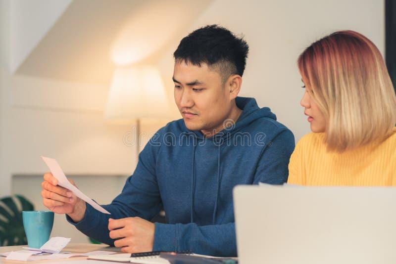 Les jeunes ont souligné des finances de gestion de couples asiatiques, passant en revue leurs comptes bancaires utilisant l'ordin photographie stock libre de droits