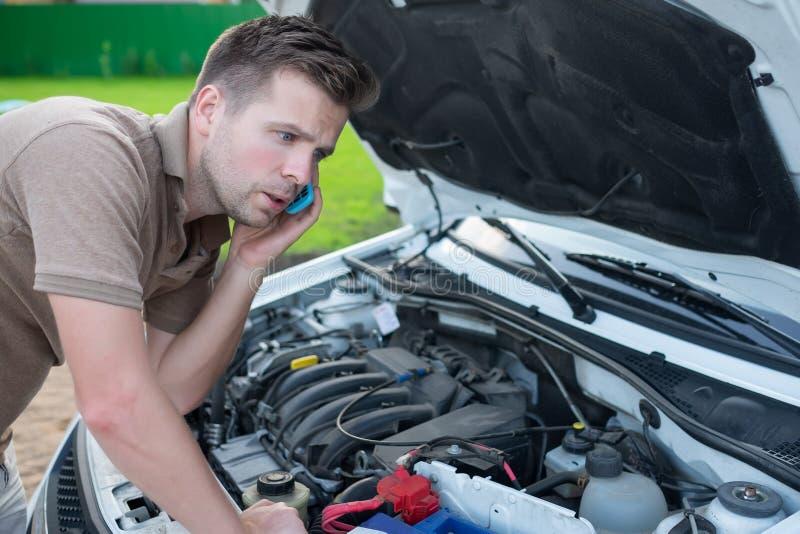 Les jeunes ont soumis à une contrainte l'homme ayant des ennuis avec sa voiture cassée regardant dans la frustration et réclamant image stock