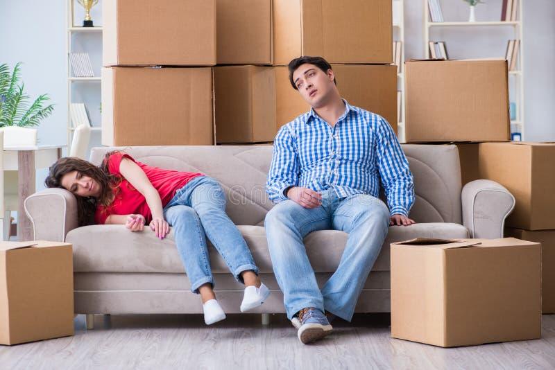 Les jeunes paires se déplaçant dedans à la nouvelle maison avec des boîtes photographie stock