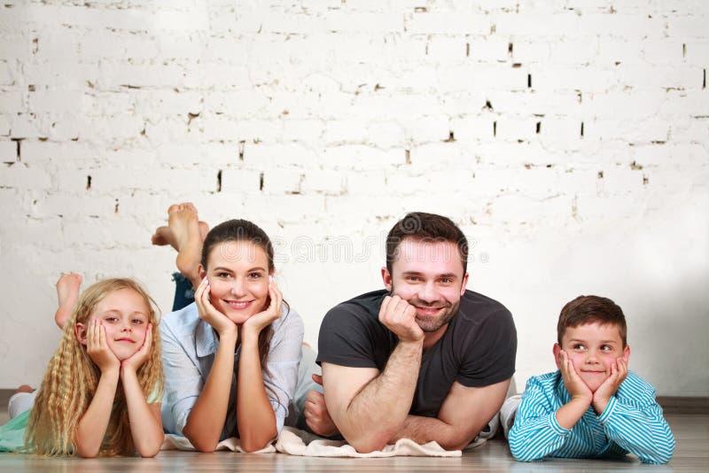 Les jeunes parents heureux de famille et deux enfants autoguident le studio images libres de droits
