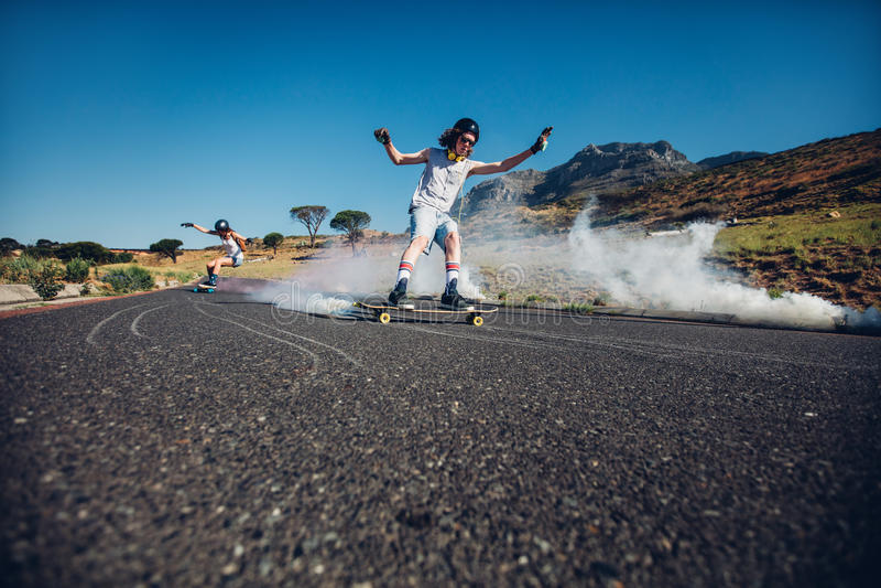 Les jeunes patinant en bas de la rue photos libres de droits