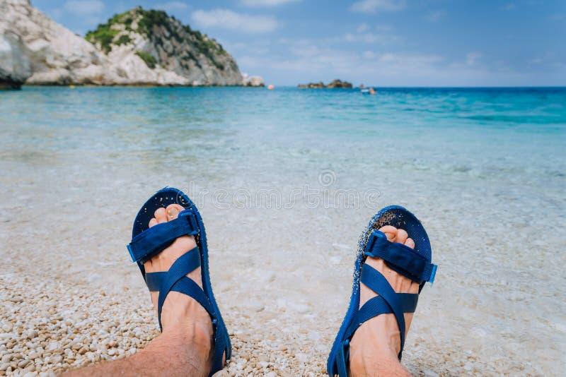 Les jeunes pieds masculins portent la sandale bleue de bascule prenant un bain de soleil sur Pebble Beach devant l'eau et les roc photo stock