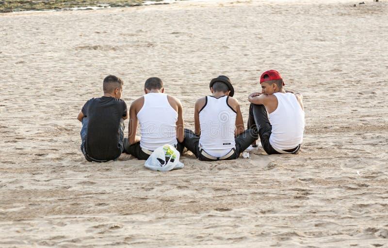 Les jeunes portant des réservoirs de Bro s'asseyent à la plage photo libre de droits