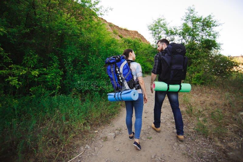Les jeunes randonneurs de couples dans la forêt folâtre l'homme et la femme avec des sacs à dos sur la route en nature image libre de droits