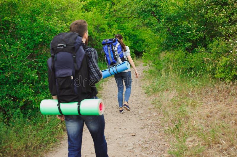 Les jeunes randonneurs de couples dans la forêt folâtre l'homme et la femme avec des sacs à dos sur la route en nature image stock