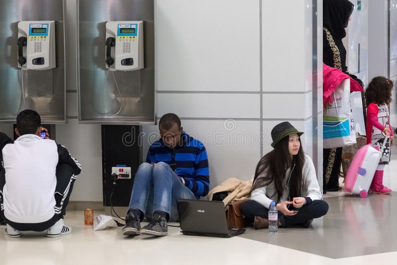 Les jeunes s'asseyant sur le plancher et attendant leur vol à l'aéroport international de Doha photographie stock libre de droits
