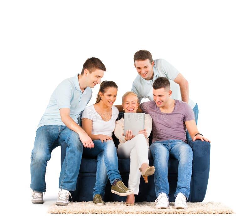 Les jeunes s'asseyant sur un sofa, regardant une tablette photo stock