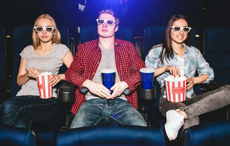 Les jeunes s'asseyent dans les chaises dans le cinéma Ils portent des lunettes pour des films de observation Le type a la tasse d images stock