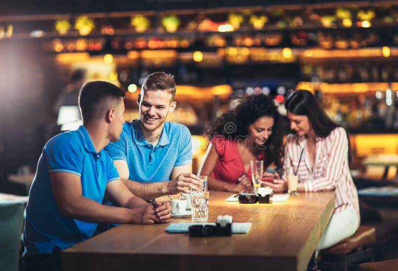 Les jeunes se réunissant dans un café, utilisant le téléphone photographie stock