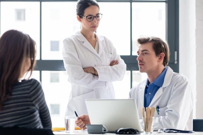 Les jeunes soignent écouter un médecin expérimenté tout en consultant un patient photos stock
