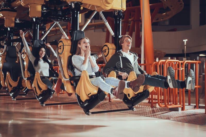 Les jeunes sont enchantés avec le parc d'attractions photo stock
