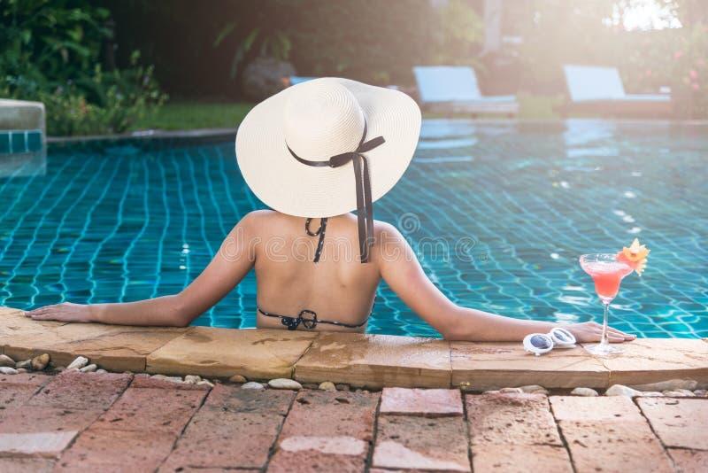 Les jeunes soutiennent la femme en cocktail de boissons de piscine de bikini photos libres de droits