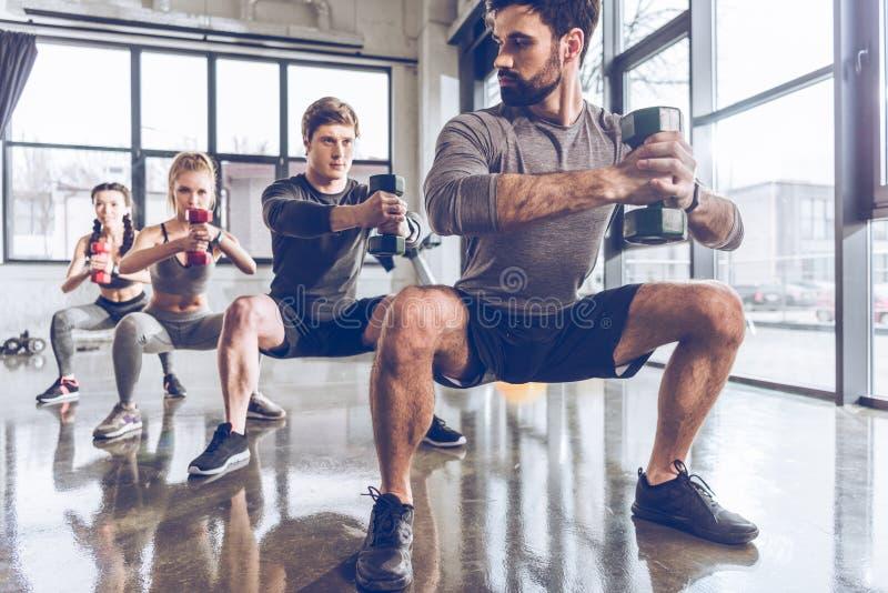 Les jeunes sportifs dans les vêtements de sport avec des haltères s'exerçant au gymnase photo libre de droits