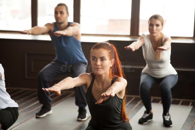 Les jeunes sportifs faisant l'exercice accroupi au traini de forme physique de groupe images stock