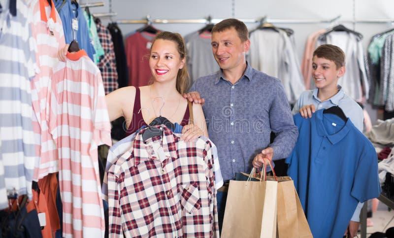 Les jeunes supports heureux de clients de famille s'approchent des vêtements photos stock