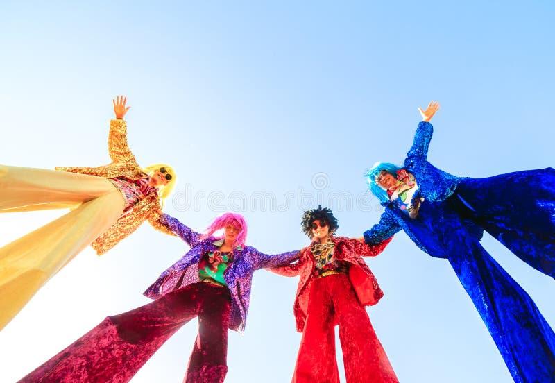 Les jeunes sur des échasses posant contre le ciel bleu photo libre de droits
