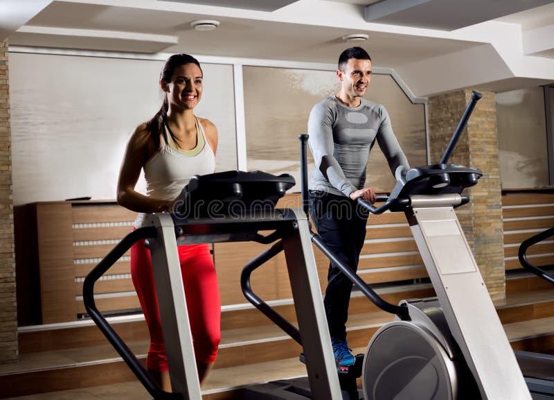 Les jeunes sur la machine d'exercice dans faire de gymnase cardio- image stock