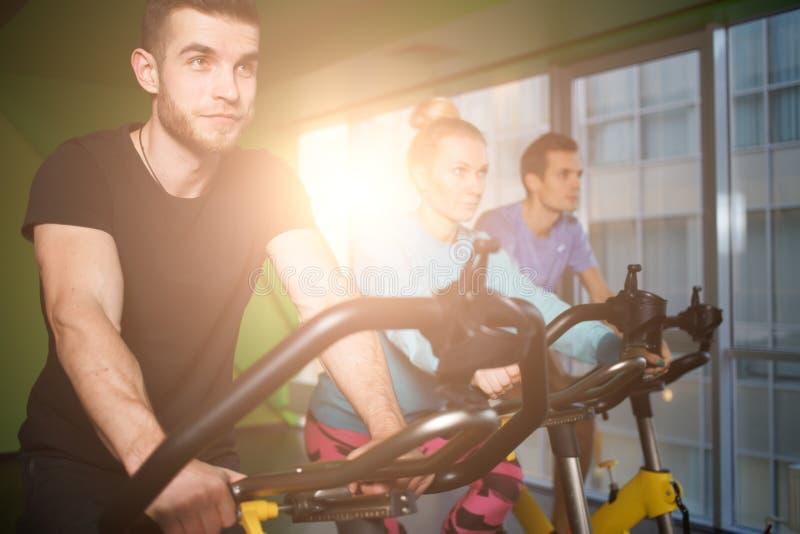 Les jeunes sur le vélo stationnaire photos libres de droits