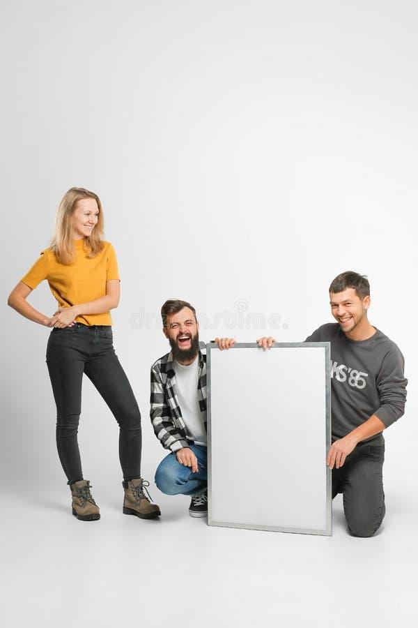 Les jeunes tenant le conseil blanc photos stock