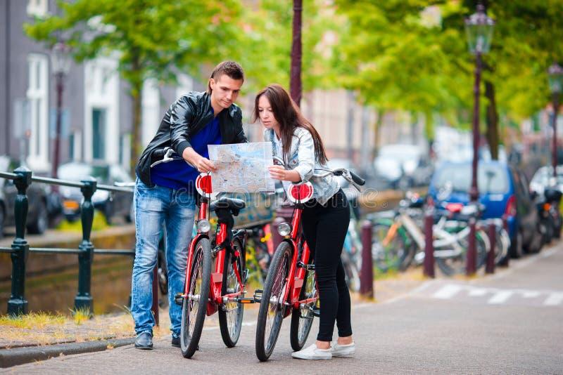 Les jeunes touristes couplent regarder la carte avec des vélos dans la ville européenne images stock