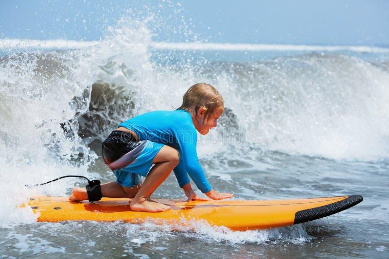 Les jeunes tours de surfer sur la planche de surf avec l'amusement sur la mer ondule photo libre de droits