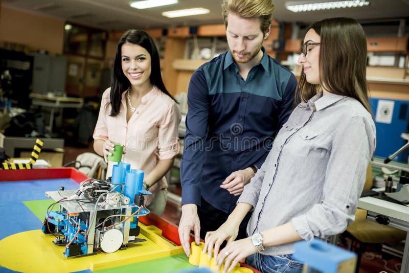 Les jeunes travaillant dans la salle de classe de robotique image stock
