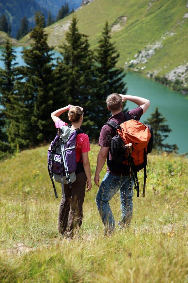 Les jeunes trimardant dans les montagnes images stock