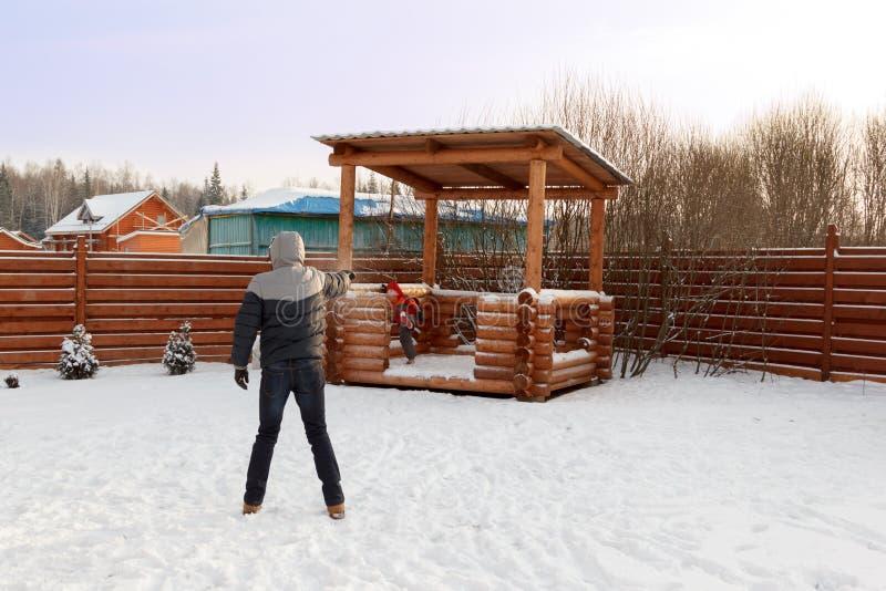 Les jeux de père avec l'enfant lance des boules de neige dans l'arrière-cour image libre de droits