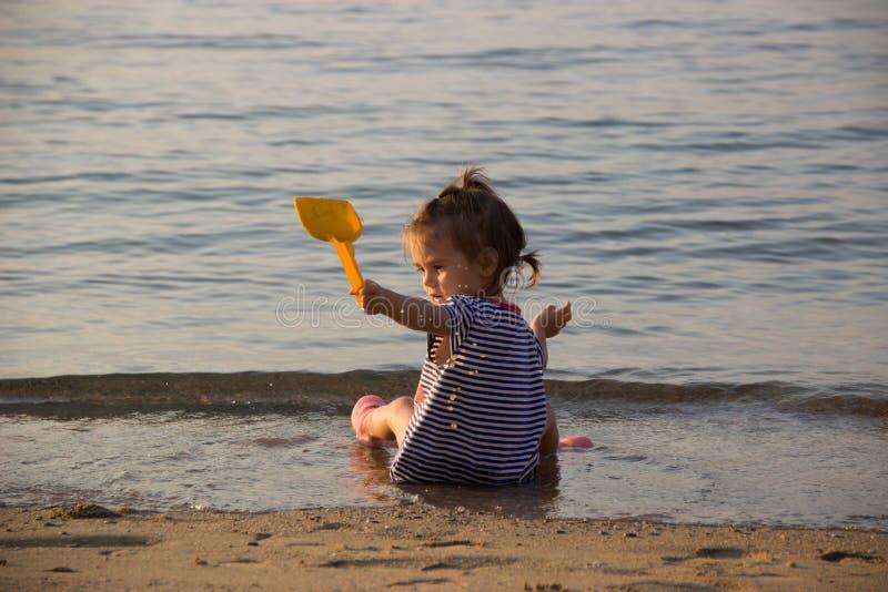 Les jeux de petite fille sur la plage avec de l'eau la pelle et à ` d'enfants éclaboussent photo stock