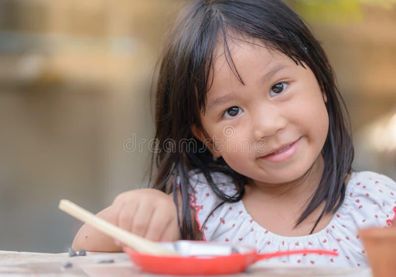Les jeux de sourire de petite fille font cuire sur la table images stock