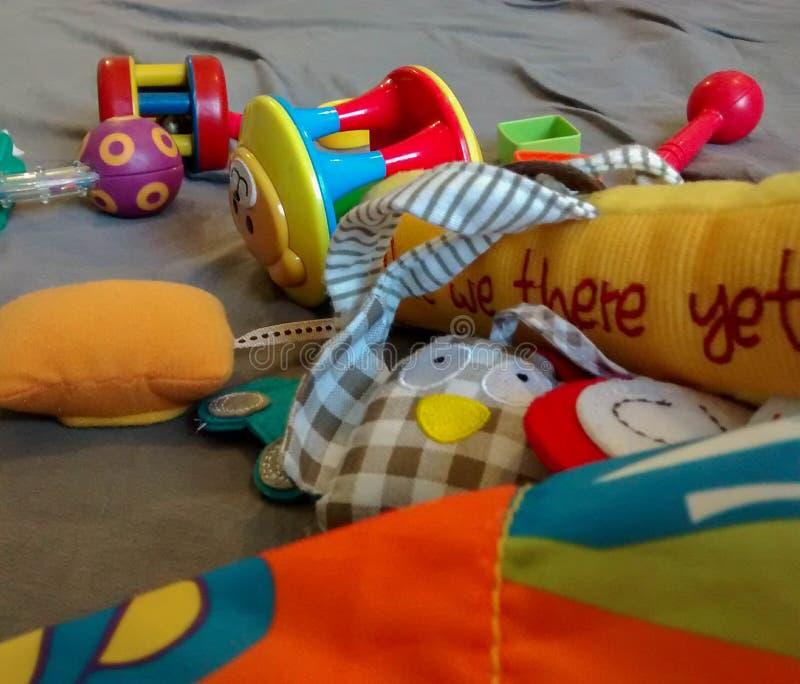 Les jouets colorés assortis de bébé ont dispersé sur le tapis de jeu photo libre de droits