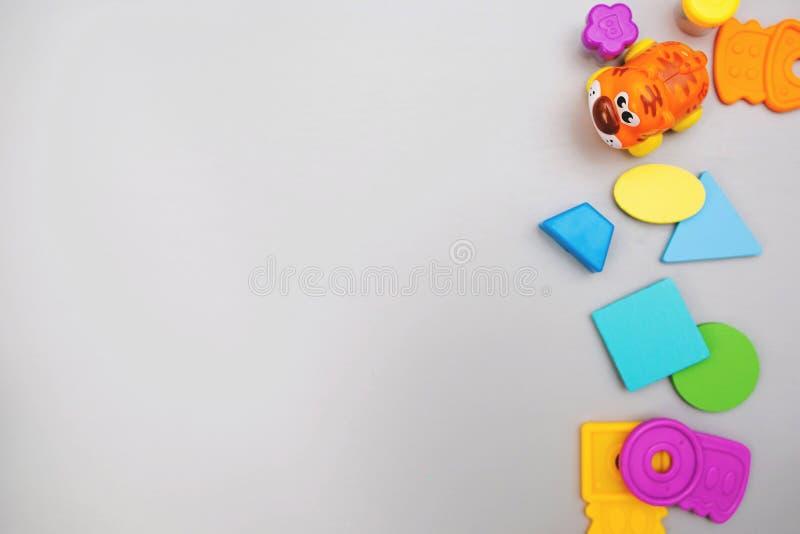 Les jouets color?s des enfants sur un fond gris avec l'espace pour le texte Configuration plate, vue sup?rieure photos stock