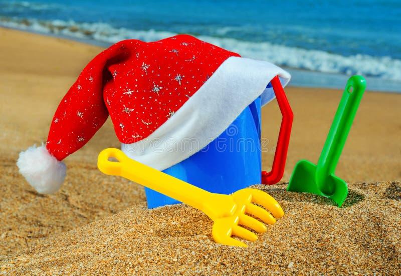 Les jouets des enfants et le capuchon du père noël sur la plage photographie stock