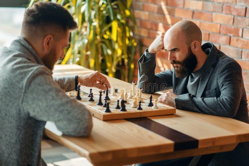 Les joueurs d'échecs masculins, déplacent l'éléphant noir photographie stock libre de droits