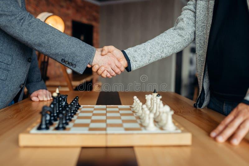 Les joueurs d'échecs masculins se serrent la main avant le jeu photo libre de droits