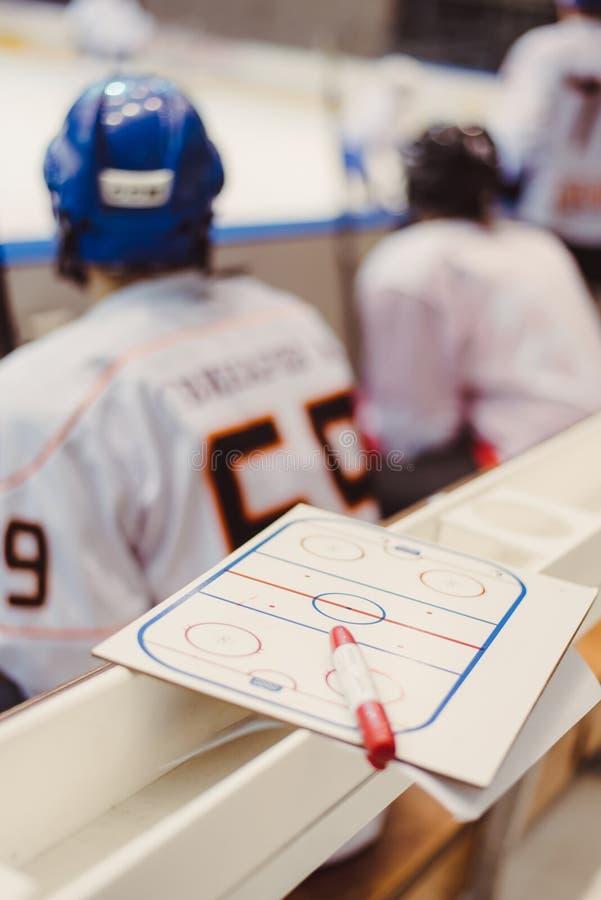 Les joueurs de hockey s'asseyent sur le banc pendant le match image libre de droits