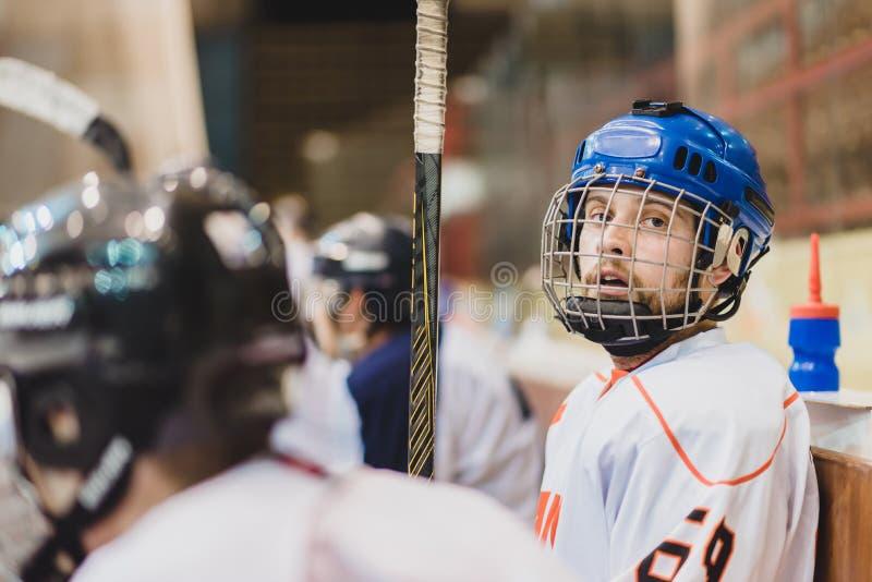 Les joueurs de hockey s'asseyent sur le banc pendant le match photos stock