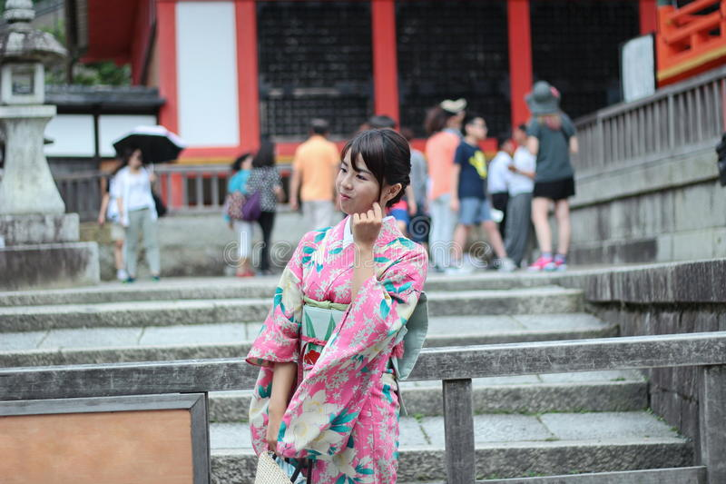 Les kimonos du ` s de femmes signalent et sourient pour la photo dans Fushimi Inari SH photographie stock libre de droits