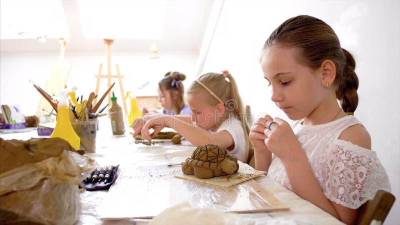 Les in kunstworkshop in basisschool De jonge geitjes modelleren speelgoed van klei stock afbeelding