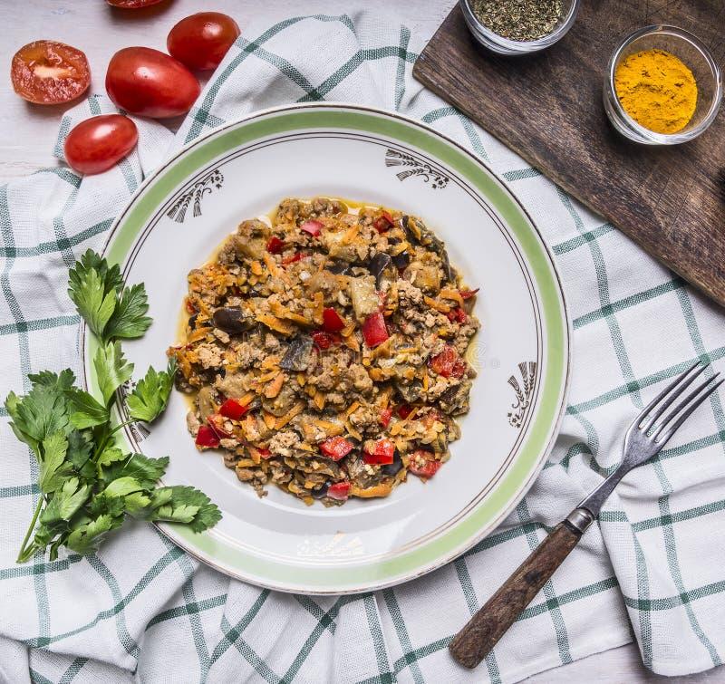 Les légumes appétissants d'agneau d'un plat blanc avec la tomate et le persil ont assaisonné et fourchette sur une fin à carreaux image libre de droits