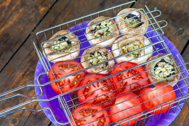 Les légumes crus dans un gril grillent pour faire cuire sur un feu photographie stock libre de droits