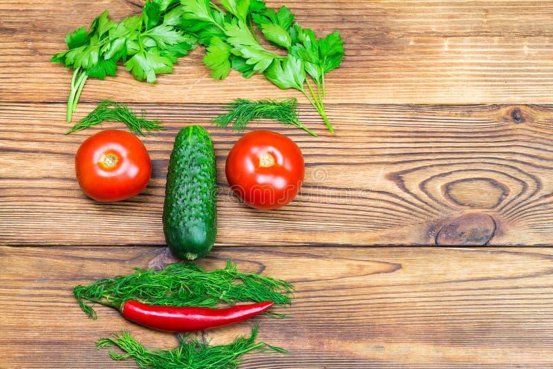 Les légumes d'arrière-cour, les tomates, le concombre, le poivre de piments et les herbes sous forme d'hommes se dirigent sur le  photographie stock libre de droits