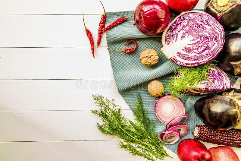 Les légumes et le fruit pourpres crus sur le fond en bois blanc avec la copie espacent la vue supérieure images stock