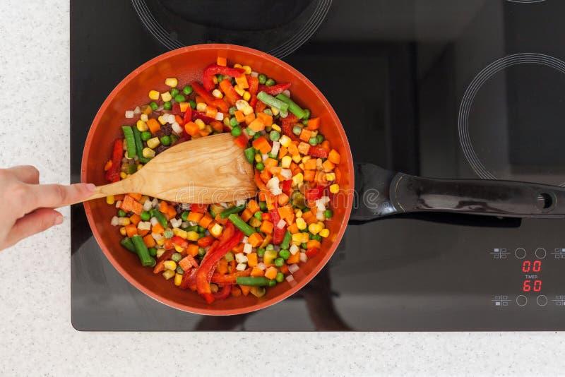 Les légumes sont dans une poêle Femme faisant cuire les légumes frais colorés sur un fourneau électrique photos stock