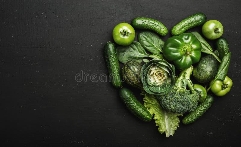 Les légumes verts frais ont arrangé dans la forme de coeur sur une table en pierre noire images stock