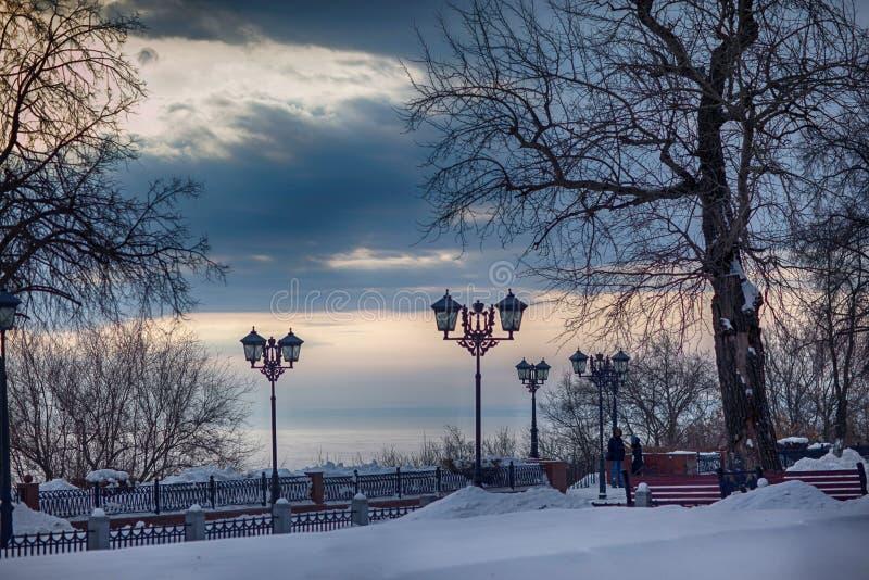 Les lanternes à l'arrière-plan de la soirée d'hiver aménagent en parc photographie stock