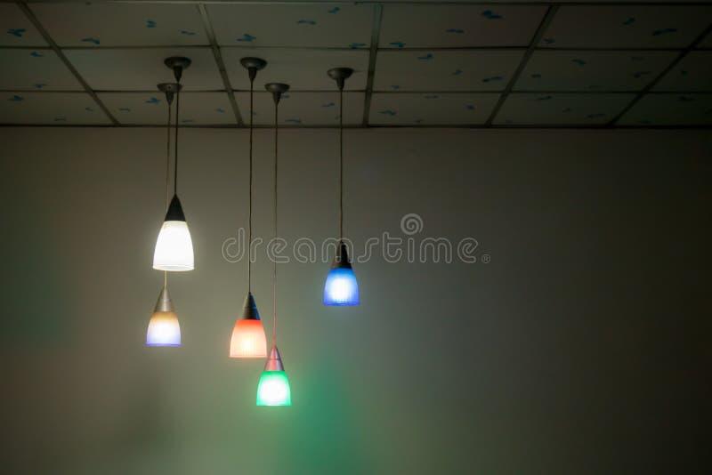 Les lanternes de allumage colorées accrochent sur le plafond dans la chambre noire photographie stock